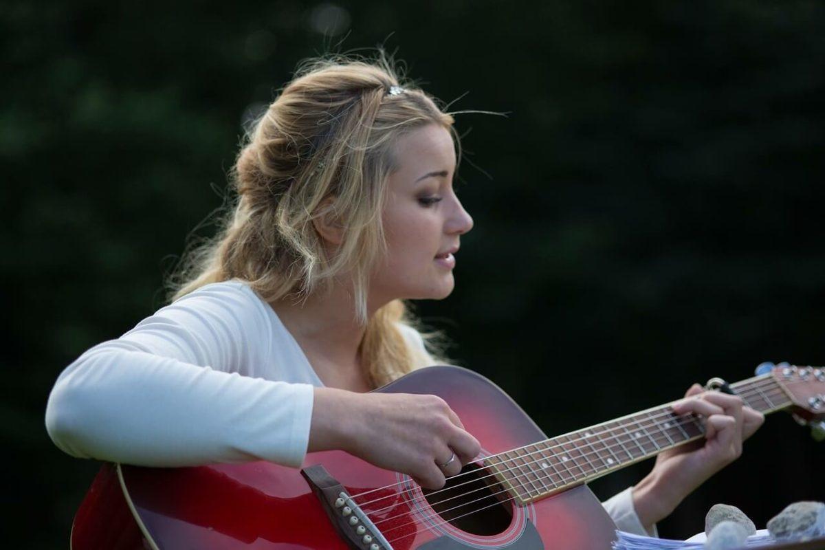 ギターで歌う女性